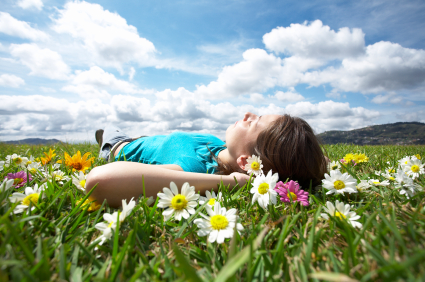 Young woman relaxing in a meadow of daisies with a blue sky and puffy clouds above her; for a representation of sedation dentistry from Sugar Land dentist Siny Thomas, DMD.