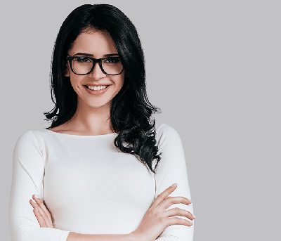 Young brunette woman with glasses standing relaxed with arms crossed; for info on overcoming dental anxiety.