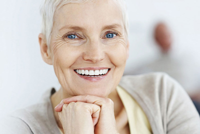 Senior woman with short gray hair; for information on the dental implant process.