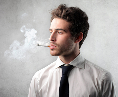 Young man wearing a shirt and tie and smoking; for information on tobacco use and dental implants.