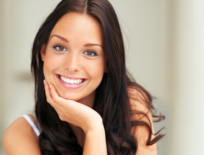 Young brunette woman with long hair smiling; for information on gum recession treatment.