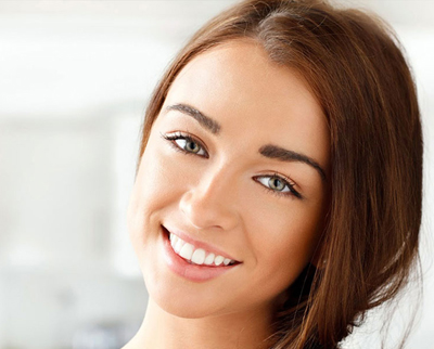 Young brunette girl smiling; for information on a perfect smile with dental implants.