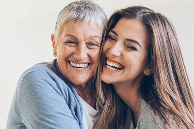 Photo of a grandmother and grandaughter smiling and hugging; for information on pinhole gum recession treatment.