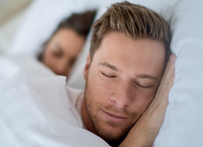 Man and woman sleeping on pillows in bed; for information on sleep apnea.