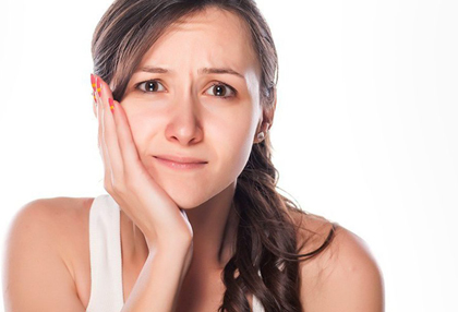 Young woman in white t-shirt holding the right side of her face due to TMJ/TMD pain.