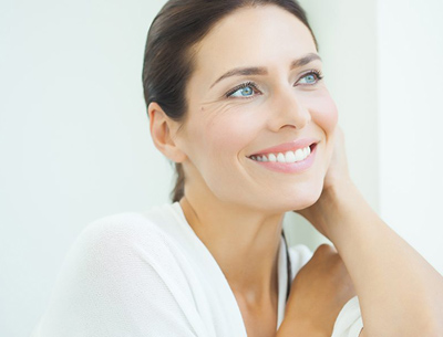 Middle-aged woman smiling; for information on when a dental crown is needed.