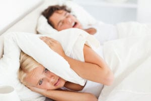 woman covering her ears from a man snoring